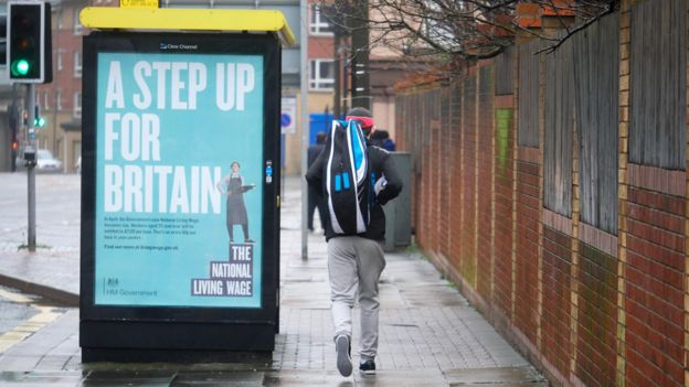 A bus stop in the city advertising the National Living Wage.