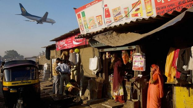 A woman talks on her cell phone as a passenger jet flies over the Jari Mari slum before landing at Mumbai Airport, on February 3, 2009 in Mumbai, India.