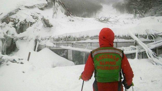 Rescatista italiano frente al lugar sepultado por la nieve.