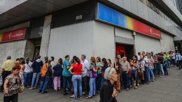 Una fila de gente frente a un banco