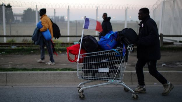A man pushes a shopping trolley carrying his belongings and a French flag