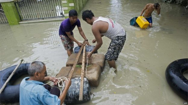 Flood-affected residents make a raft to travel through floodwaters in Kalay, upper Myanmar's Sagaing region on 3 August 2015