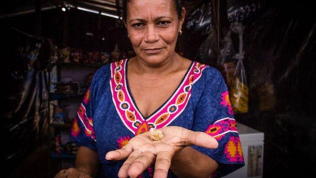 Una mujer con una pepita de oro