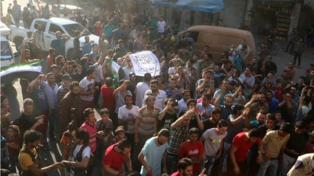 People carry a Free Syrian Army flag and a Jabhat Fatah al-Sham flag as they celebrate