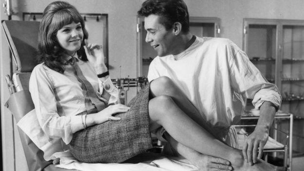 Actor Dirk Bogarde toma el pie de una actriz durante el rodaje de una película