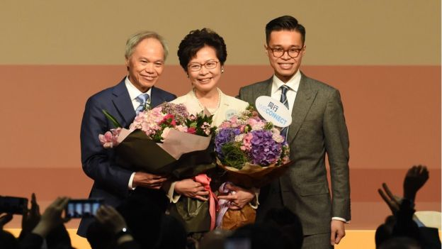 Hong Kong's new chief executive Carrie Lam (C) holds bouquets as she stands on stage after winning the Hong Kong chief executive election in Hong Kong on March 26, 2017.
