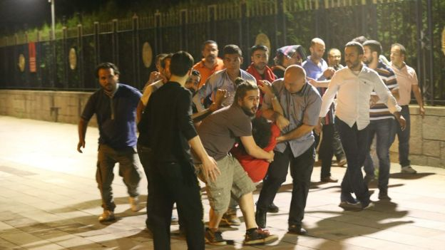 People carry an injured man in Ankara, Turkey, on 16 July 2016