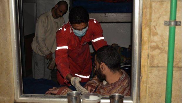 Trabajadores de la Media Luna Roja ayudan a un paciente discapacitado