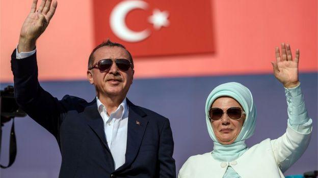 Cumhurbaşkanı Erdoğan ve eşi Emine Erdoğan kürsüden kalabalığı selamlıyor.