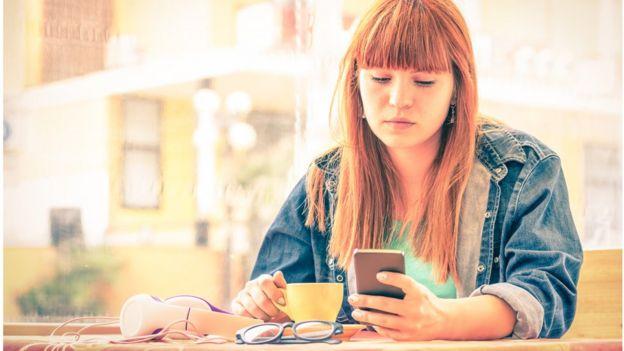 Telefonuna bakan bir kadın.