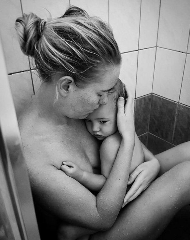 Kelli Bannister holding her daughter in the shower