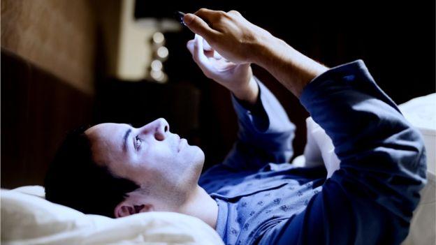 Homam usando celular na cama