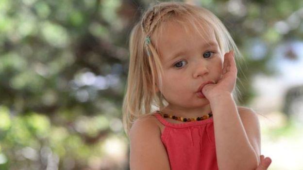 Niña rubia chupádose el dedo