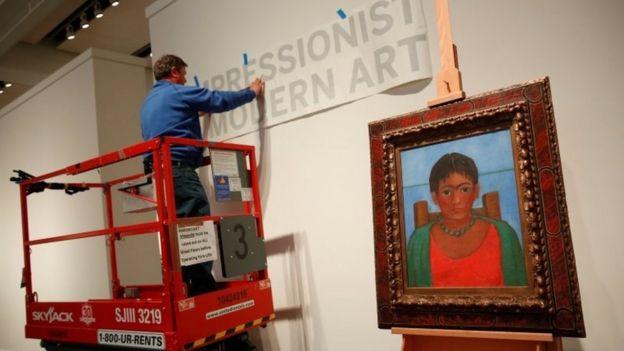 Un hombre pega una calcomanía en la pared trasera de la exhibición que mostrará el cuadro de Frida Kahlo, que también aparece en la foto con un marco antiguo.