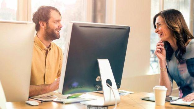 Hombre y mujer sentados en una oficina, que conversan y sonríen
