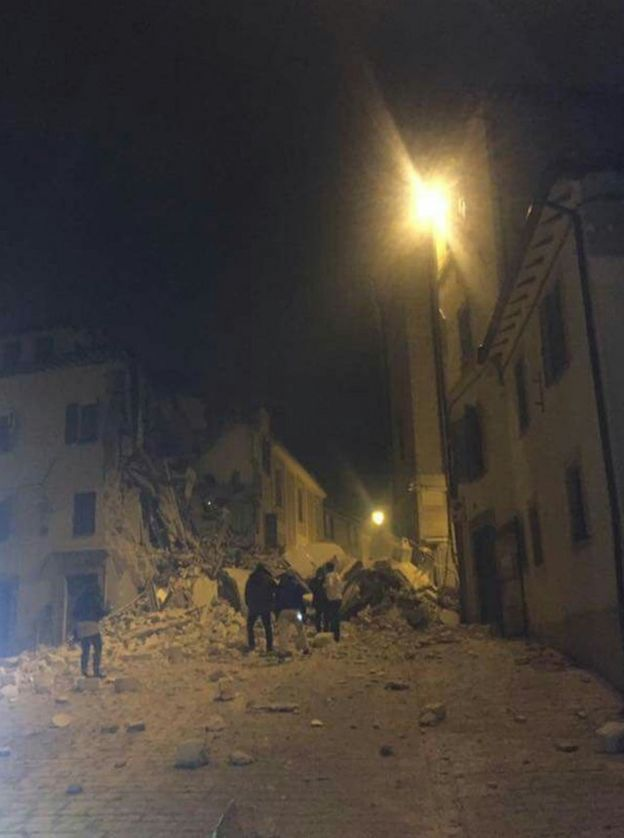 rubble from a collapsed building filling a lamp-lit street in Camerino, 26 October 2016