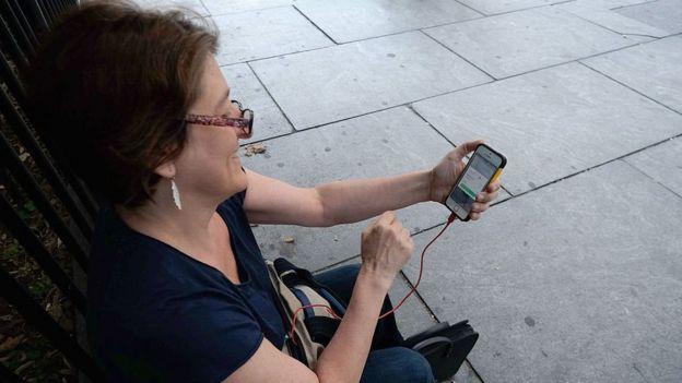 Una señora juega Pokémon Go