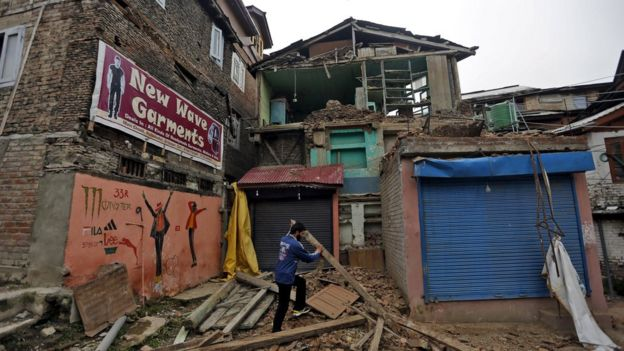A man clears debris after his house partially collapsed following an earthquake, in Srinagar, India April 10, 2016