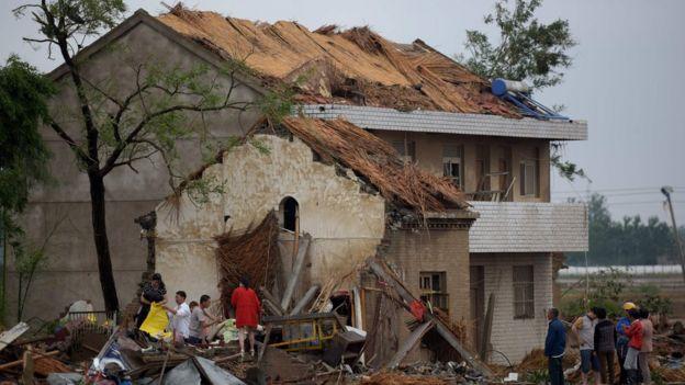 Pobladores caminan entre las ruinas de las casas que dejó el tornado en Funing, Yancheng, en la provincia de Jiangsu.