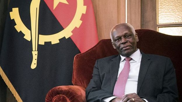 President dos santos sitting in a chair with Angolan flag in the background