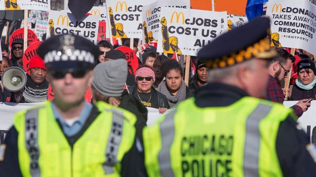 Police keep watch as demonstrators demanding an increase in the minimum wage to $15-dollars-per-hour march in the streets on April 14, 2016 in Chicago