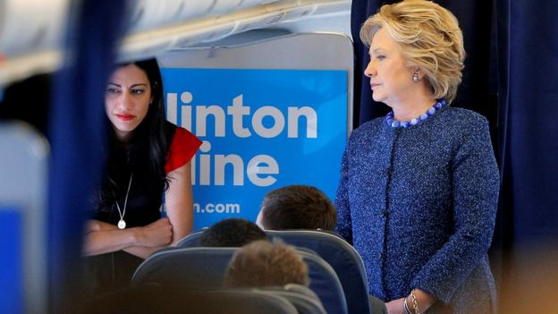 U.S. Democratic presidential nominee Hillary Clinton talks to staff members, including aide Huma Abedin (L), onboard her campaign plane in White Plains, New York, U.S. October 28, 2016