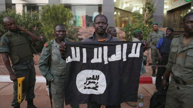Malian security officials show a jihadist flag they said belonged to attackers in front of the Radisson hotel in Bamako.
