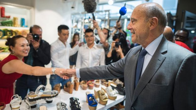 French right-wing Les Republicains (LR) party's mayor of Bordeaux and candidate for the LR party primary Alain Juppe (R) shakes hands during a visit to the Chinese community in Aubervilliers, near to Paris, on September 8, 2016.