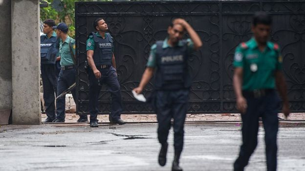 Bangladeshi policemen exit from a gate leading to an upscale cafe in Dhaka on July 03, 2016
