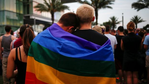 Men, draped in rainbow flag embrace ahead of candle light vigil in memory of victims of shooting at Pulse gay night club in Orlando, Florida. 13 June 2016