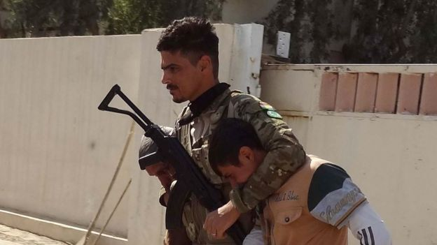 A Kurdish fighter escorts a prisoner in Kirkuk, 22 October