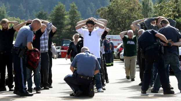 Police search students outside Umpqua Community College in Roseburg, Ore., Thursday, Oct. 1, 2015, following a deadly shooting at the college.