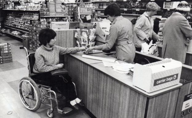 A woman from Banstead handing money over in a shop. She is a wheelchair user