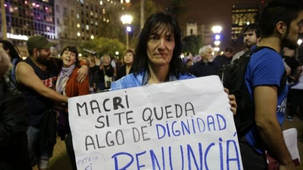 A woman holds a sign that reads in Spanish