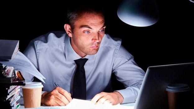 Un hombre trabajando frente a su laptop en mitad de la noche