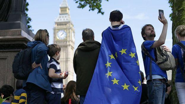 Un joven envuelto en una bandera de la UE observa el Big Ben.