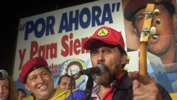 Hugo Chávez ante un cartel en el que se lee *Por ahora y para siempre*