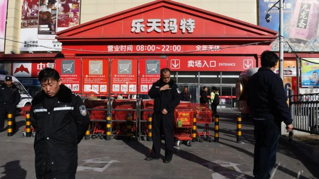 Policemen patrol outside a Lotte Mart in Beijing on March 9, 2017.