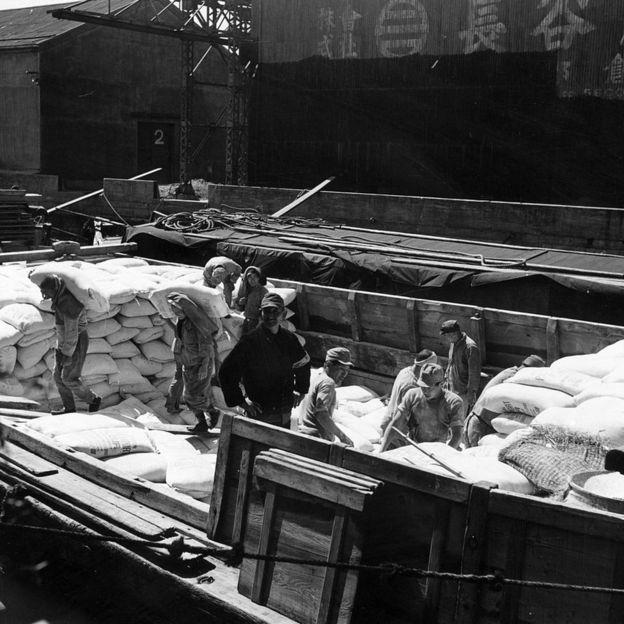 Estibadores descargan harina en un puerto de Japón en 1955.