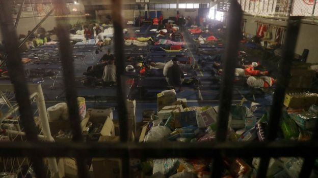 People prepare to spend the night in a makeshift camp set up inside a gymnasium