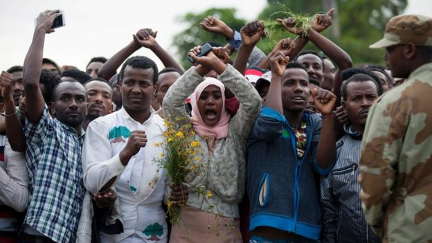 Residents of Bishoftu cross their wrists above their heads as a symbol for the Oromo anti-government protesting movement during the Oromo new year holiday Irreechaa in Bishoftu on October 2, 2016 shows