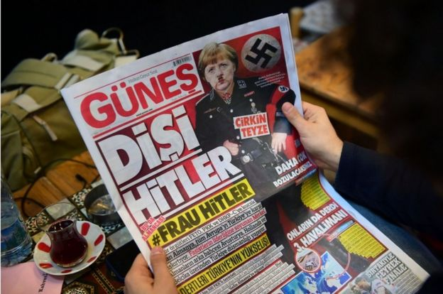A man reads an issue of Gunes, a Turkish pro-government daily newspaper, with German Chancellor Angela Merkel depicted in Nazi uniform
