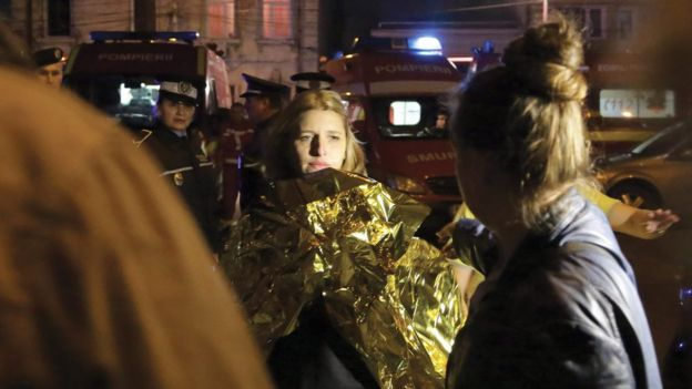 A Romanian woman, survivor of an explosion at a club, looks on as she wears a thermal first aid foil shortly after being rescued by firefighters