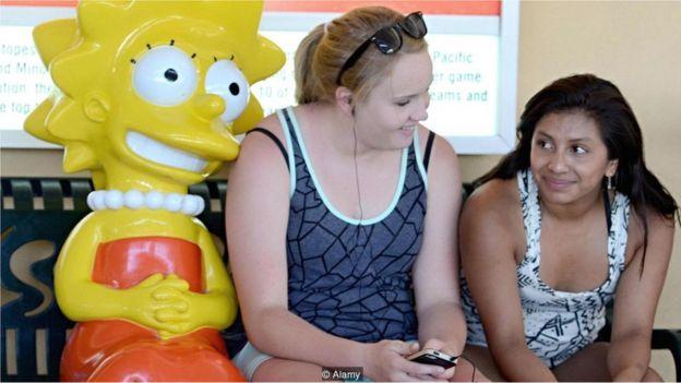 Meninas posam com estátua do personagem Lisa Simpson