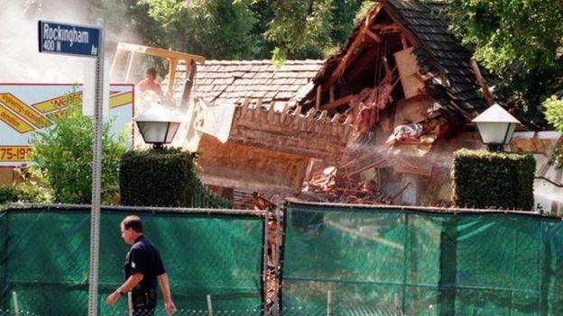 A bulldozer tears down OJ's house in July 1998