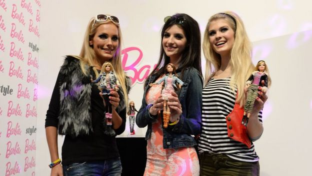 Models posing with Barbie dolls
