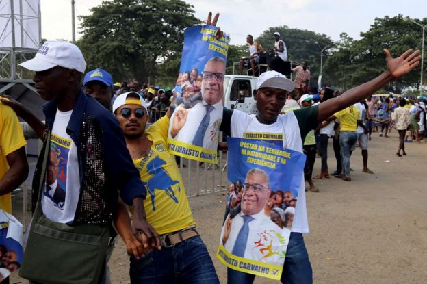 Supporters of Evaristo Carvalho wearing T-shirts and holding placards picturing the politician celebrate in Sao Tome, 18 July