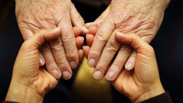 Manos jóvenes agarrando manos mayores