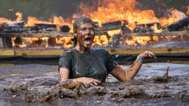woman in mud with fire in the background