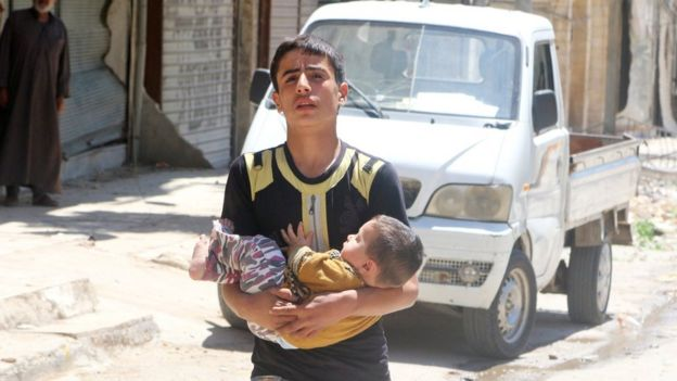 A boy carries a baby after a reported barrel bomb attack in the rebel-held Firdous district of Aleppo (29 April 2016)